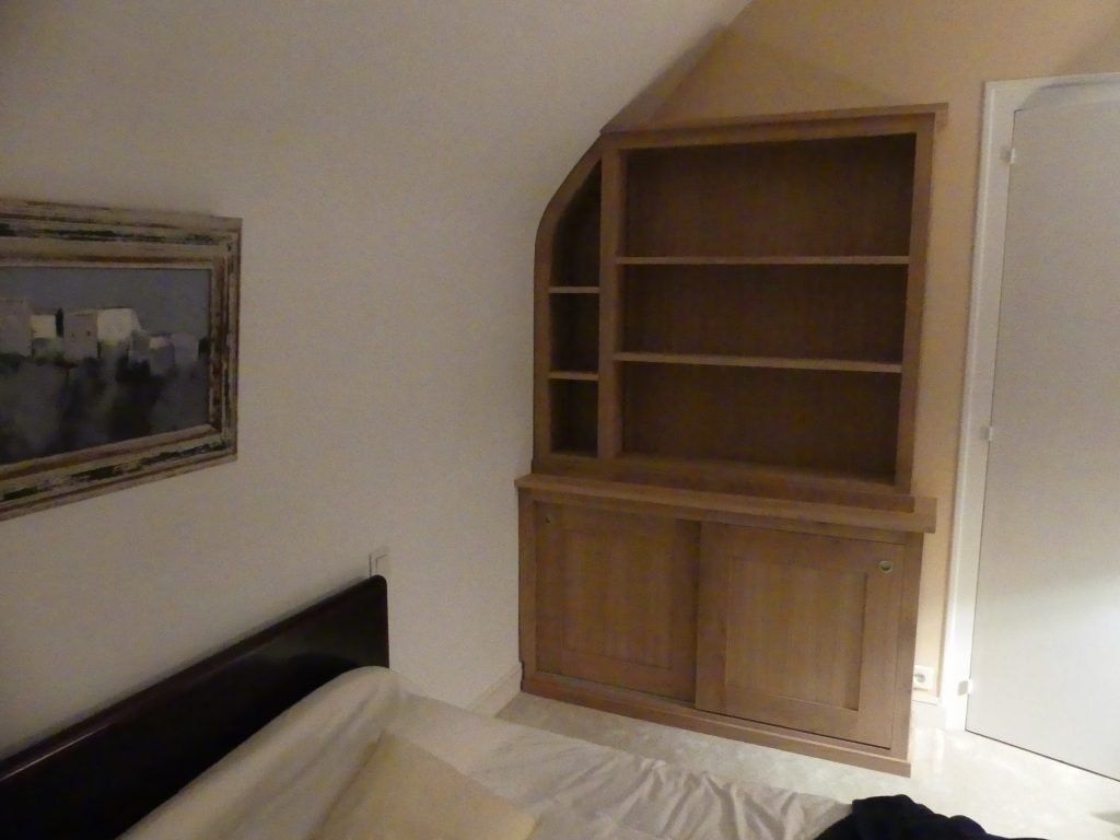 Bibliothèque en Chêne sur mesure en sous pente, portes coulissantes étagère sur crémaillère. Finition huilé